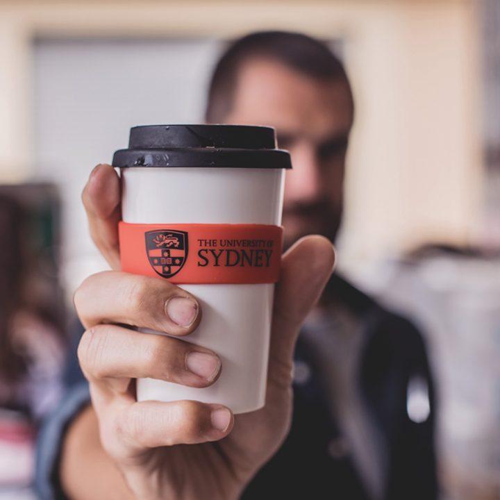 Foto de estudante segurando copo da Universidade de Sydney.