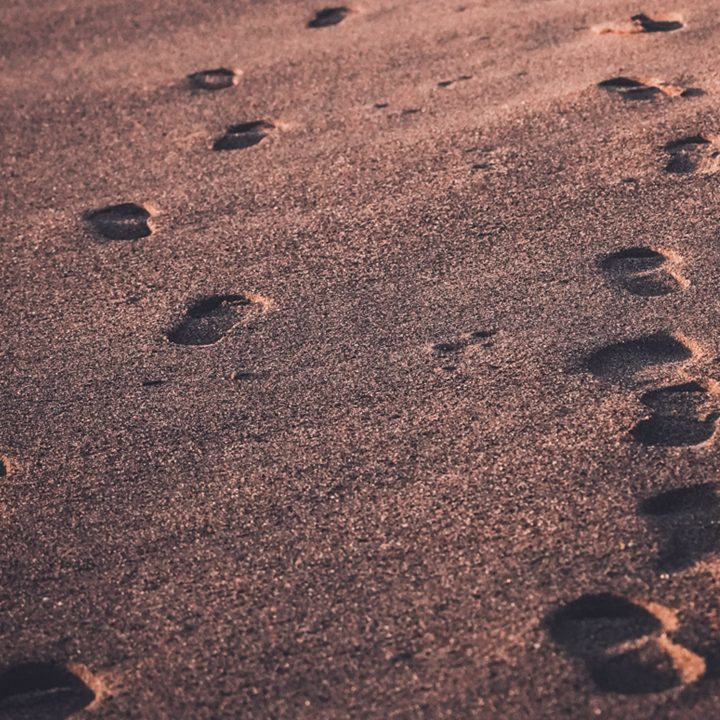 Agência de intercâmbio para vistos de estudante. Foto de pegadas na areia.