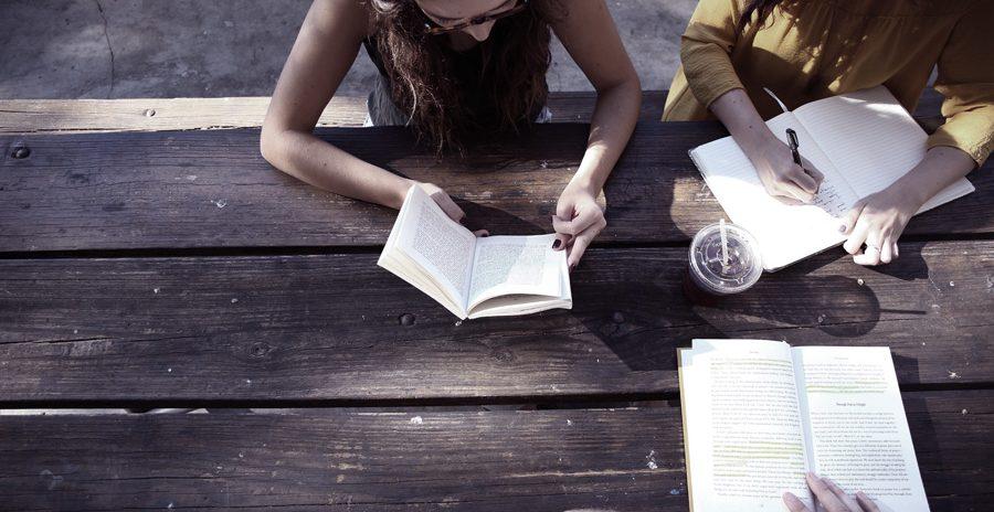estudantes lendo e escrevendo em cima de uma mesa