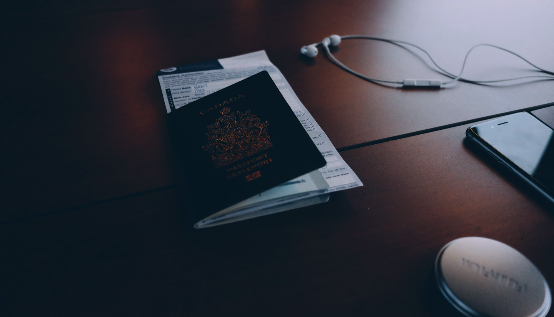 Visto para o Canadá. Foto de um passaporte canadense com uma passagem de avião dentro.